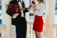 a cute Valentine's Day engagement pic with lots of red blooms to match the bridal outfit