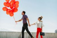 a fun Valentine's Day engagement pic with red balloons, red pants to mark the most romantic holiday of the year
