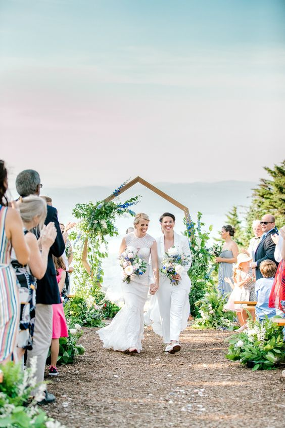 a geometric wedding arch decorated with greenery, blue and white blooms and with cool views for a summer ski resort wedding
