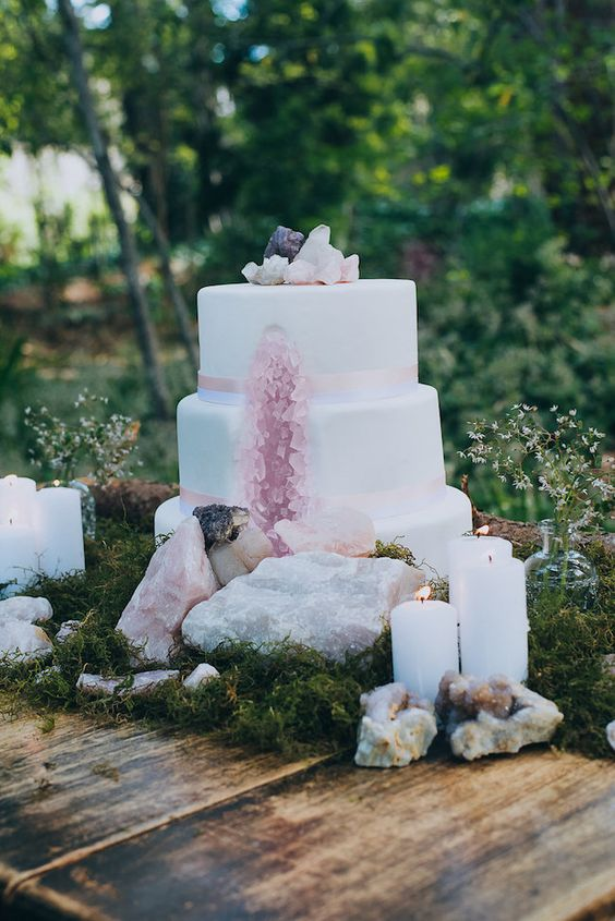 a gorgeous geode wedding cake with rose quartz and crystals on top and around the cake is very cool