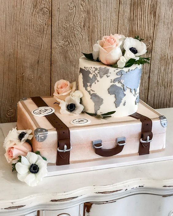 a gorgeous travel-themed wedding cake with a vintage suitcase and a world map tier plus sugar blooms