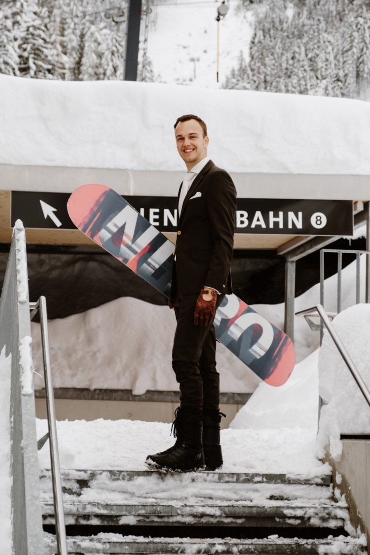 a groom in snowboarding boots, gloves and his own snowboard for a cool and inspiring wedding portrait