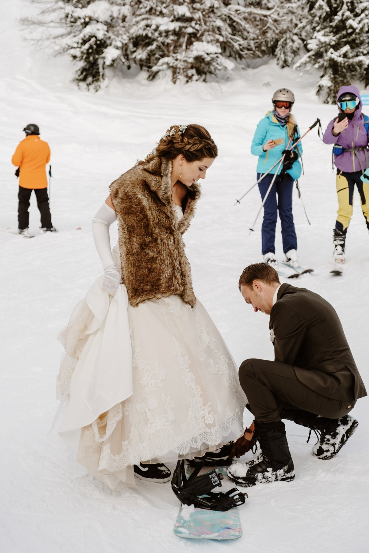 a happy couple standing on their snowboards for having fun and some cool wedding portraits