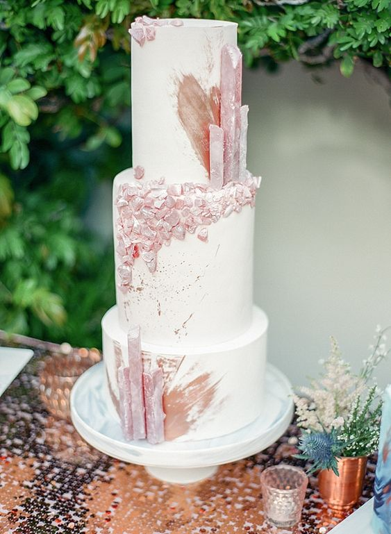 a large white wedding cake decorated with edible rose quartz and rose gold splashes is very refined and chic