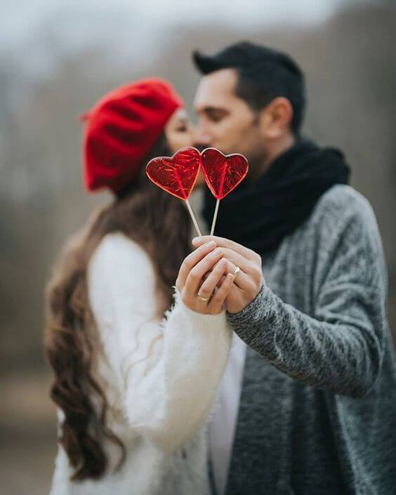 a lovely Valentine's Day engagement pic with red heart popsicles is a very cute and cool idea