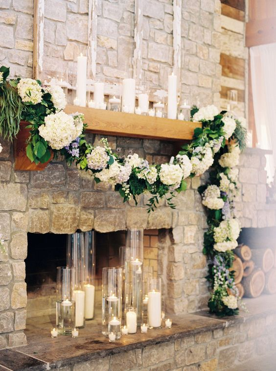a lush hydrangea and greenery garland, pillar candles and floating candles in glasses make the rough stone fireplace cooler