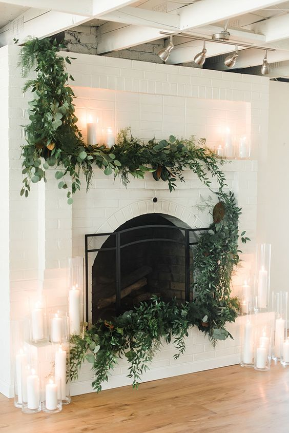 a lush textural greenery garland covering the mantel and fireplace and candles in tall glasses make it look modern and fresh