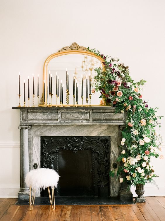 a mirror in a refined frame, tall black candles in gold candleholders and a lush greenery and bold bloom garland cascading down from the mantel