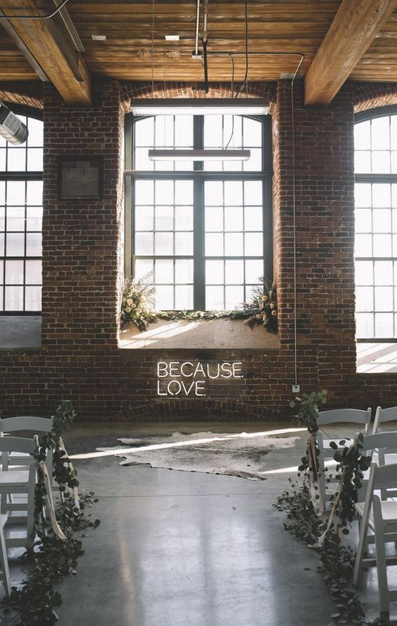 a modern industrial wedding ceremony space with a neon sign, lush floral arrangements with greenery and a faux animal skin rug