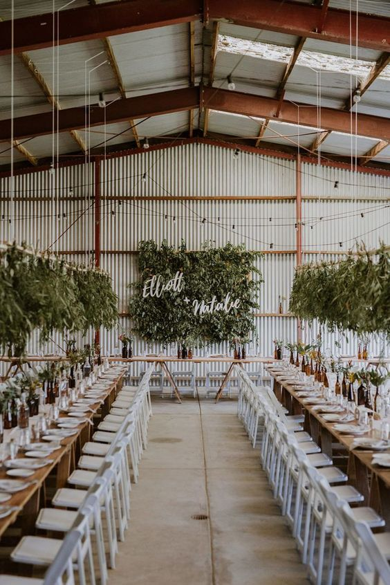 a neutral industrial wedding venue with corrugated steel walls, skylights and lots of lights and greenery