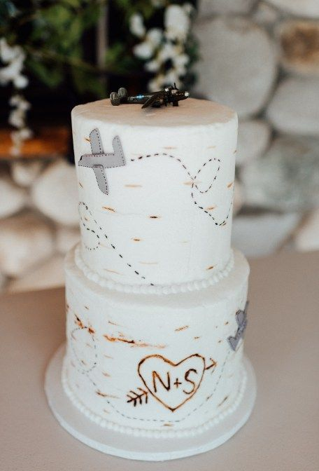 a neutral wedding cake decorated with airplanes and topped with one for travel-lovers