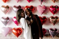 a pretty Valentine engagement pic with a heart balloon wall, bride-to-be wearing red polka dot shoes