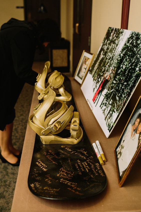 a real snowboard in black and gold as a wedding guest book is a very fun and cool idea for such a wedding