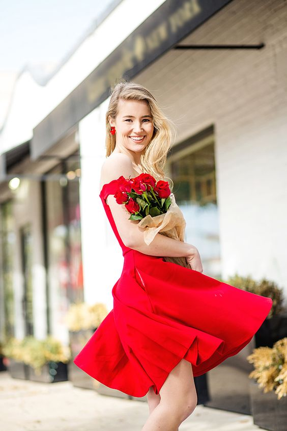 a red off the shoulder over the knee A-line dress, statement earrings and red roses for a bride-to-be