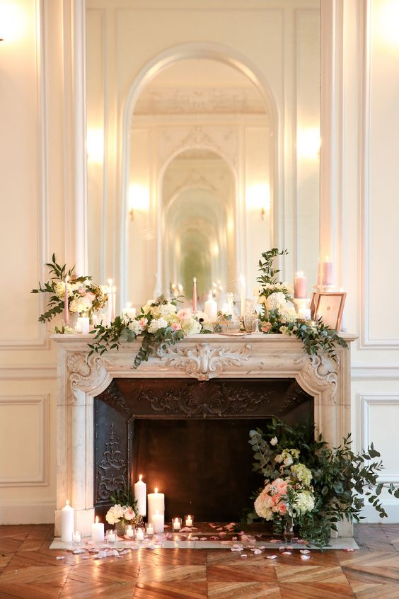 a refined vintage fireplace with lush florals, greenery and candles plus a large mirror