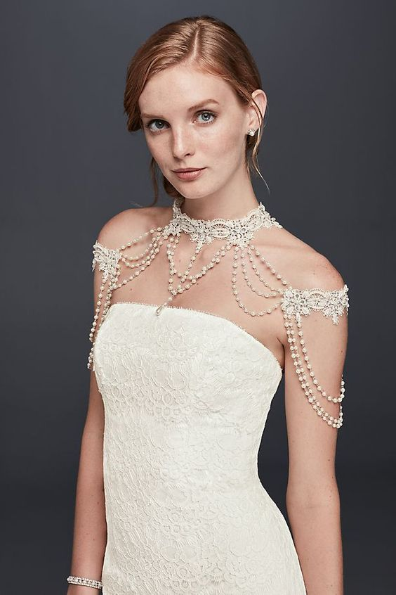 a refined white lace and pearls shoulder jewelry piece paired with a lace sheath wedding dress for a chic vintage look