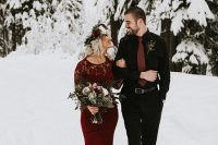 a romantic snowy Valentine engagement with a burgundy sheath dress with a lace bodice and a groom-to-be wearing a black look with a rust tie