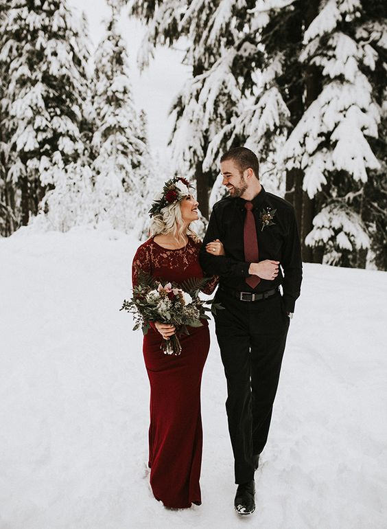 a romantic snowy Valentine engagement with a burgundy sheath dress with a lace bodice and a groom to be wearing a black look with a rust tie
