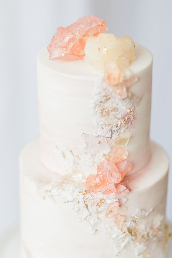 a romantic white wedding cake decorated with rose quartz and more textures for a cool look