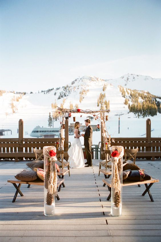 a rustic ski resort wedding ceremony space with a wooden arch, red blooms and pinecones and benches with pillows