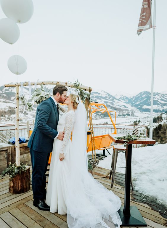 a rustic wedding arch of birch wood, greenery and neutral blooms with lovely views of the moutains is cool
