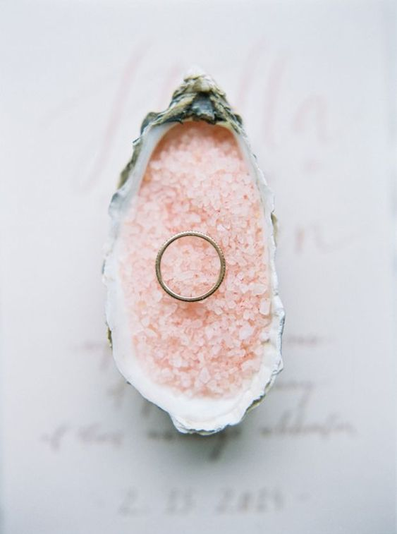 a seashell filled with pink Himalayan salt to display a wedding ring is a cool fit for a rose quartz wedding