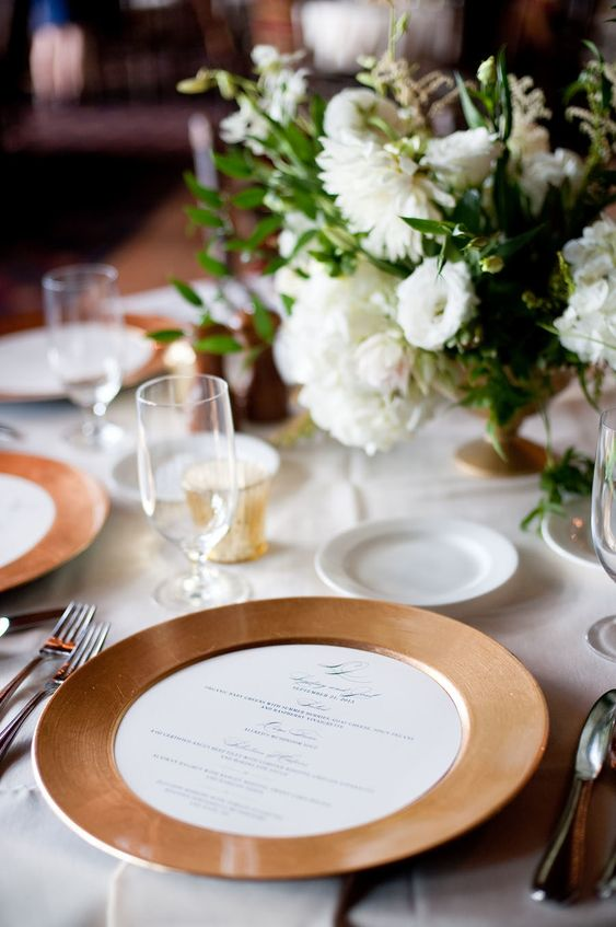 a simple and elegant wedding tablescape with terracotta chargers, white blooms and greenery and candles