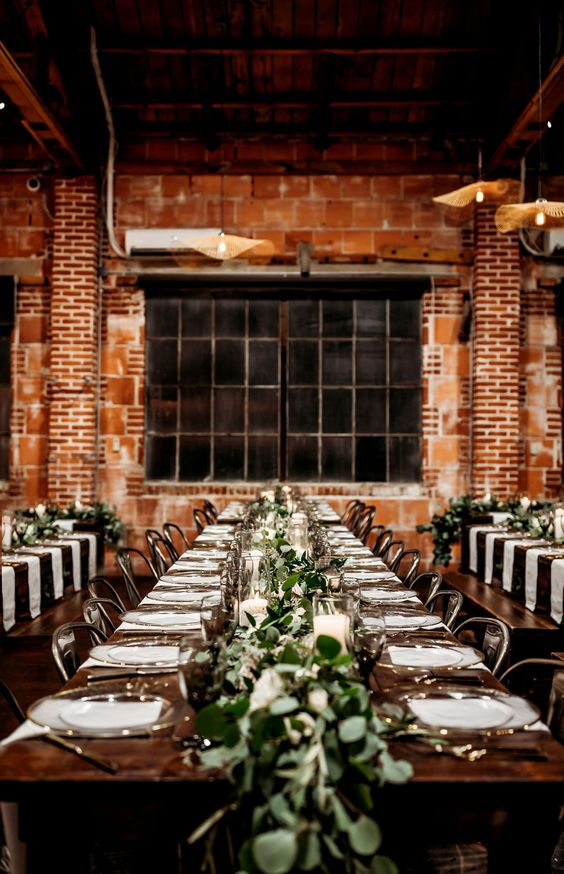 a simple industrial wedding venue with brick walls, metal pendant lamps, greenery runners and candles