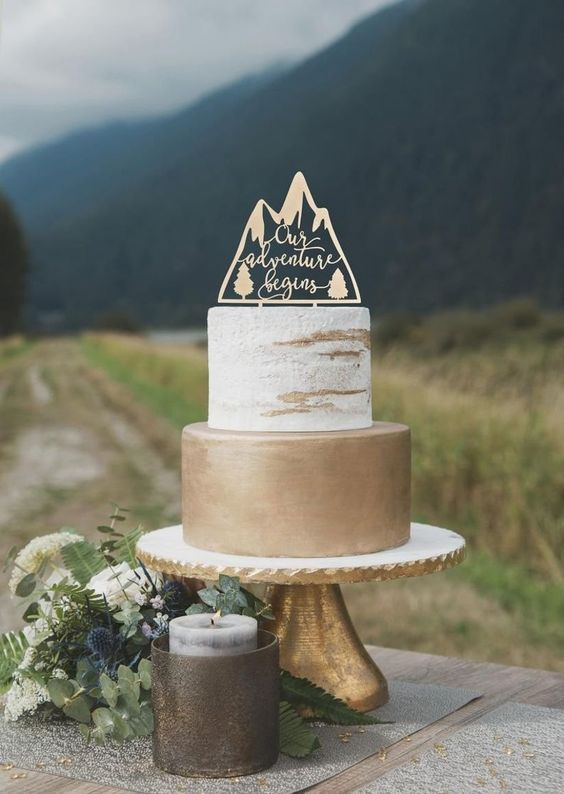 a ski resort or mountain wedding cake with a naked tier and a gold one and with a laser cut topper