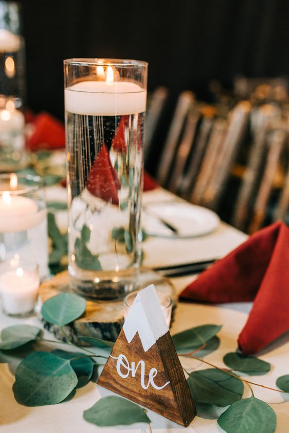 a ski resort wedding tablescape with floating candles, greenery, red napkins and a mountain table number is cool
