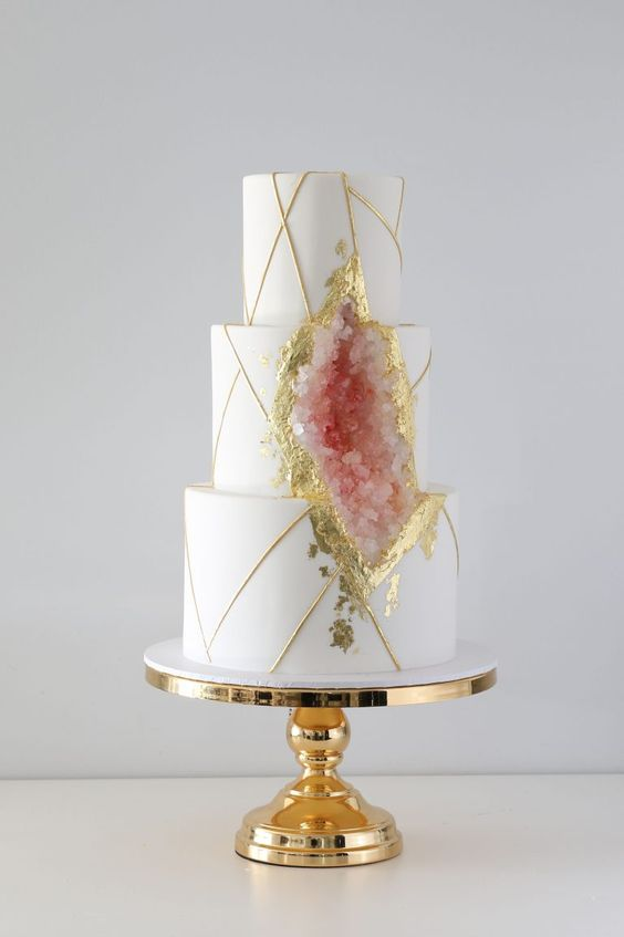 a sophisticated white wedding cake with gold touches and rose quartz plus gold leaf around it looks very chic