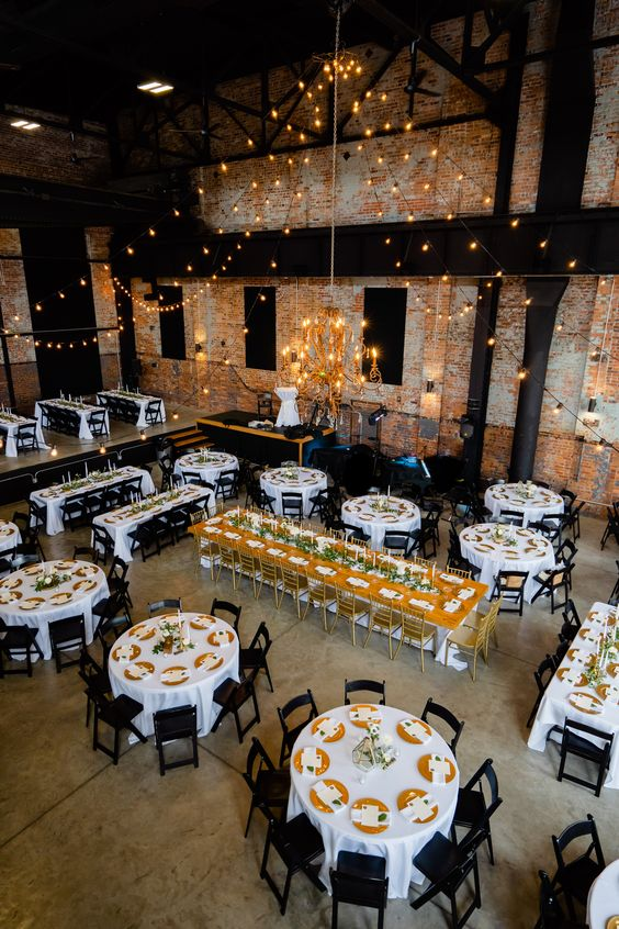 a spacious industrial wedding venue with brick walls, wooden and metal beams, lights, elegant tables