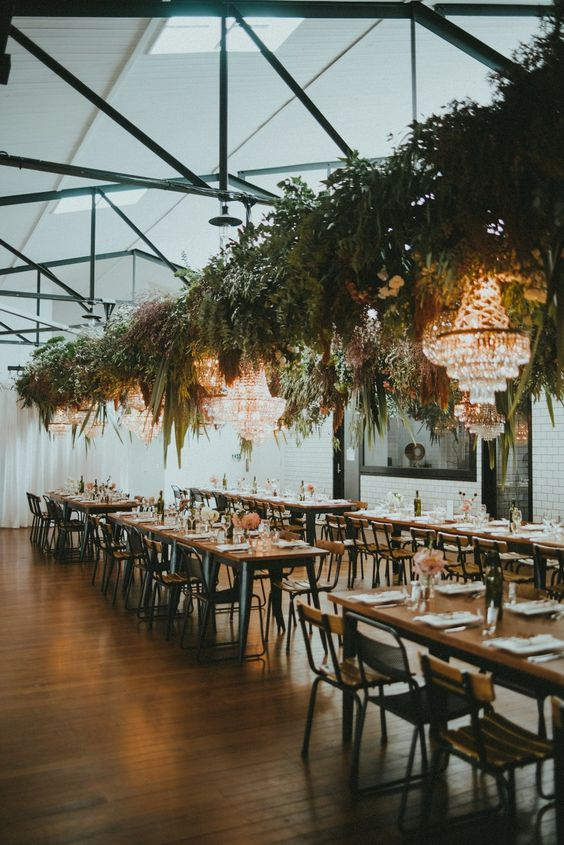 a stylish industrial venue with skylights, exposed metals, refined chandeliers, greenery installations