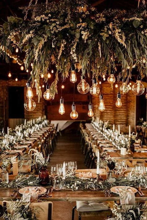 a stylish industrial wedding reception space with a greenery chandelier, white blooms and hanging bulbs plus candles on the table