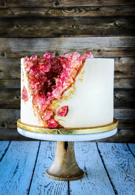 a very catchy geode wedding cake with rose quartz and gold leaf is bold and cool