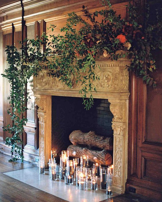 a vintage refined fireplace with dark candles, firewood and lush foliage on the mantel