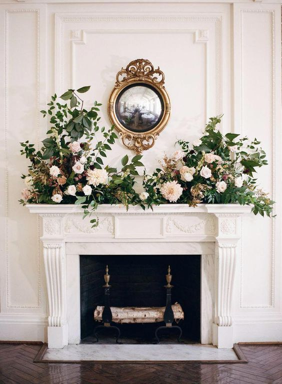 a wall-mounted mirror in a refined frame, blush and neutral blooms and greenery for an exxquisite and stylish look