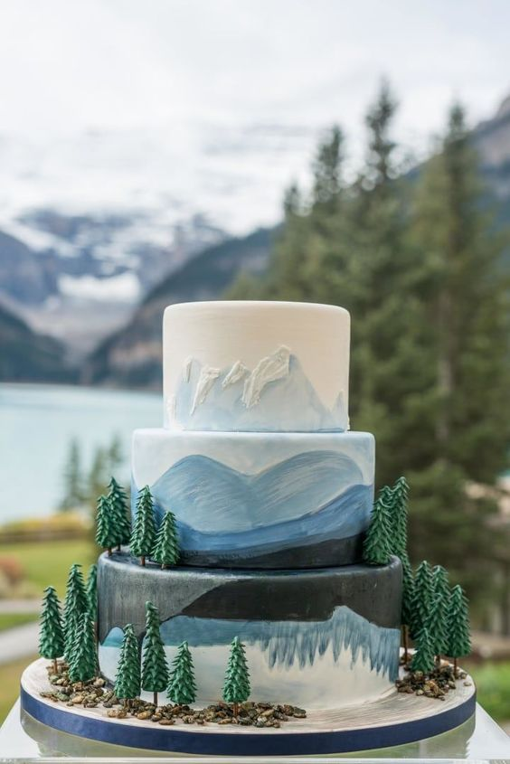 a watercolor white, blue and black cake with fir trees and painted mountains is an amazing idea for a ski resort wedding