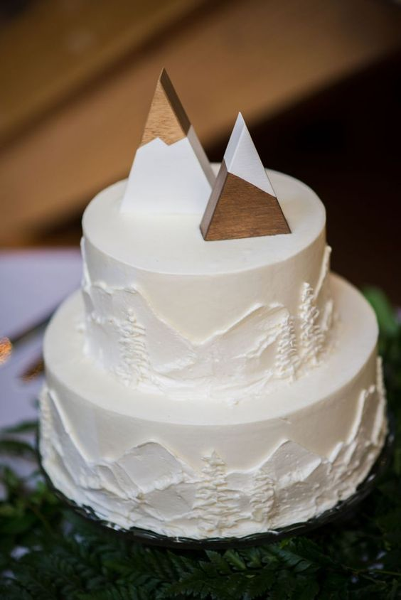 a white buttercream wedding showing mountains and fir trees, with wooden mountain like toppers is cool