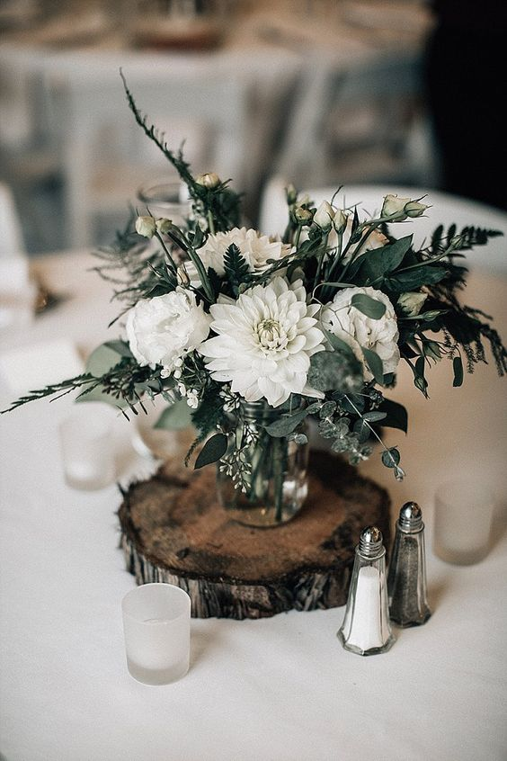 a white floral centerpiece with greenery and candles around placed on a wooden slice is a good decor idea for a ski resort wedding
