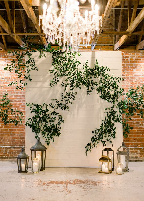 a white plank wedding backdrop decorated with greenery, crystal chandeliers, candle lanterns on the floor