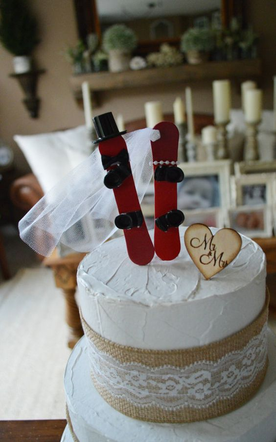 a white textural wedding cake with burlap and lace, a wood heart and red snowboards on top for a cute touch