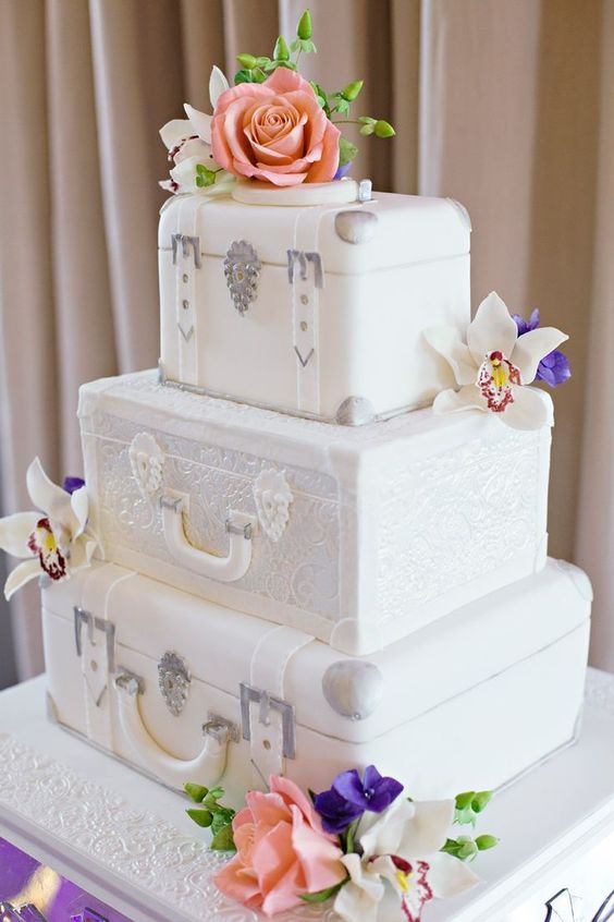 a white wedding cake featuring vintage suitcase tiers and bright fresh blooms for a bold look