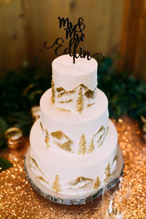a white wedding cake with gold fir trees and mountains, a calligraphy topper is a chic idea for a ski resort wedding