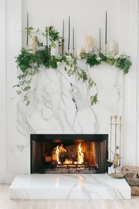 agate candleholders, tall thin candles in metallic candleholders and lush greenery and white blooms plus marble cladding for a modern feel