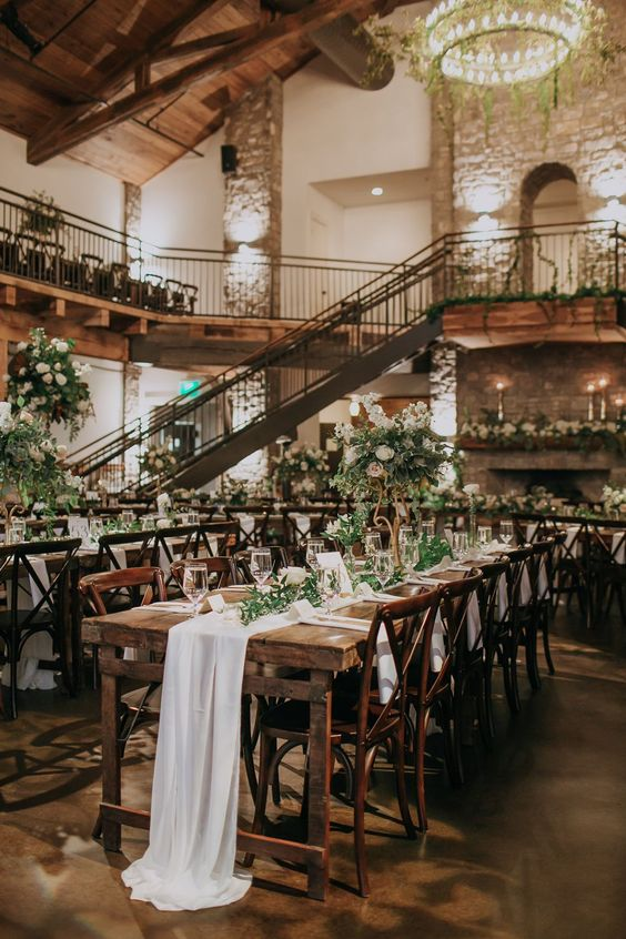 an elegant rustic ski resort reception with greenery and white blooms, white linens and candles is amazing