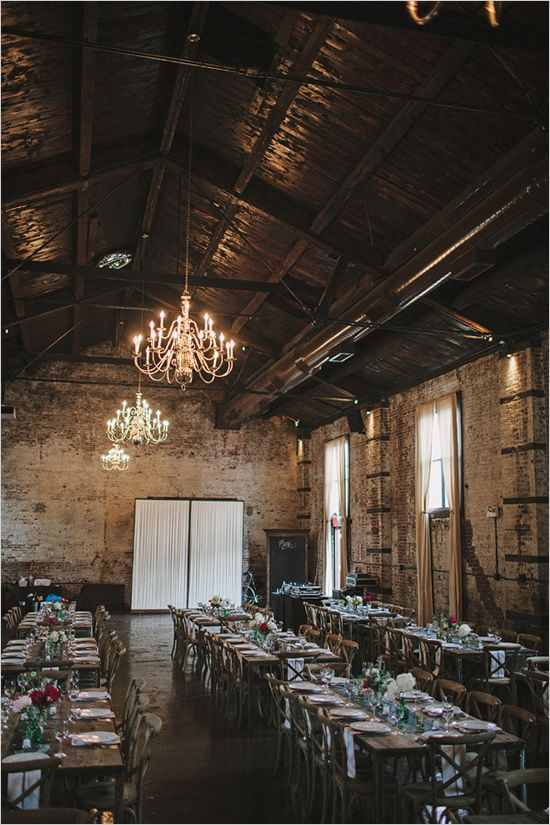 an elegant wedding venue with brick walls, exposed pipes and chandeliers plus bright blooms on the table