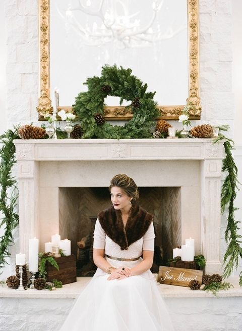 an evergreen garland and wreath plus large pinecones, wooden boxes and signs, some white blooms and candles