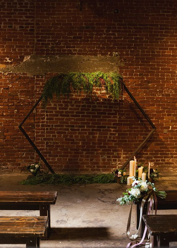 an industrial meets rustic space with a hex arch with greenery, wooden benches, candles and blooms