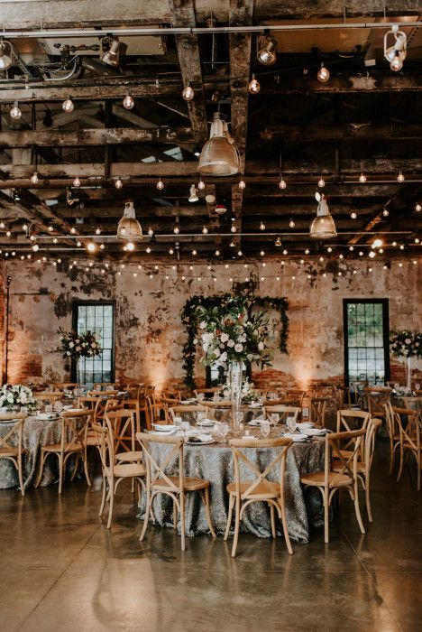 an industrial reception space with brick walls, exposed pipes, lights and pendant lamps and neutral blooms